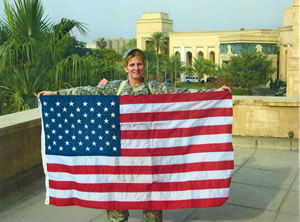 CW5 Geri Bowers holding up flag that was flown specificially for Tom Stevens